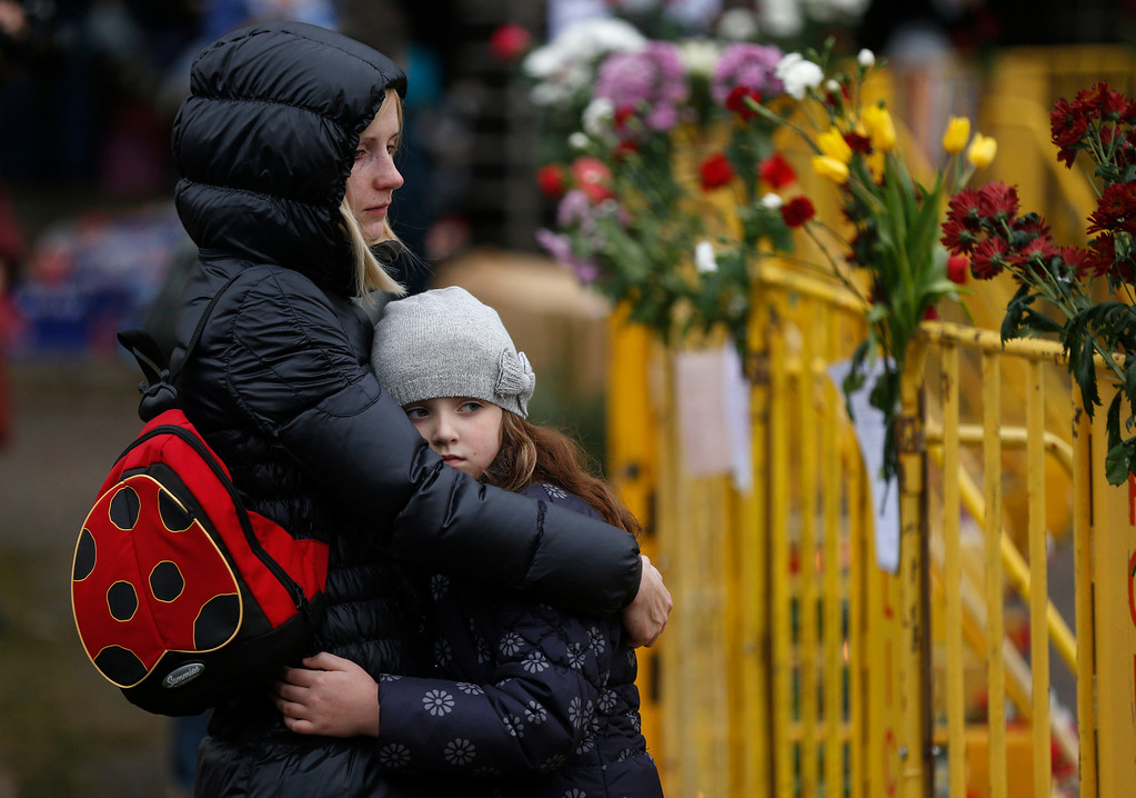 . Passers by react outside the collapsed Maxima supermarket in Riga, Latvia, Saturday, Nov. 23, 2013.  Scores of people have died, including three firefighters, after an enormous section of roof collapsed at a Latvian supermarket in the country\'s capital, emergency medical officials said Friday.  (AP Photo/Mindaugas Kulbis)