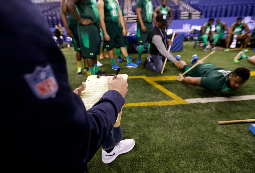 . Chicago Bears area scout Breck Ackley jots down Ohio State defensive lineman Mike Bennett\'s measurements at the NFL football scouting combine in Indianapolis, Sunday, Feb. 22, 2015. (AP Photo/Julio Cortez)
