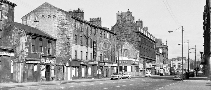 Eglinton St, west side, north of Wallace St.    The tall building beyond Nelson St had been the second Bridge St railway station (1890), with hotel accommodation on the upper floors.    April 1973