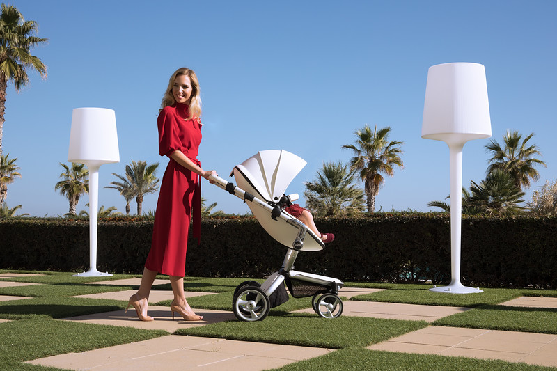 Mima_Xari_Lifestyle_Snow_White_Aluminium_Chassis_Pod_Mum_In_Red_Dress_Walking_On_Checked_Grass_Looking_Sideways.jpg