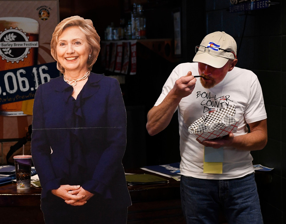 . Avid Bernie Sanders supporter Matt Brandt from Longmont Colorado gets in a bite to eat next to a cutout of Hillary Clinton at the Colorado Democratic State Convention at the Budweiser Events Center April 17, 2016. (Photo by Andy Cross/The Denver Post)