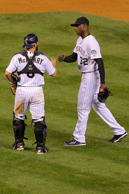 . DENVER, CO - SEPTEMBER 16:  Michael McKenry #8 of the Colorado Rockies and LaTroy Hawkins #32 celebrate their 10-4 win against the Los Angeles Dodgers at Coors Field on September 16, 2014 in Denver, Colorado. (Photo by Justin Edmonds/Getty Images)