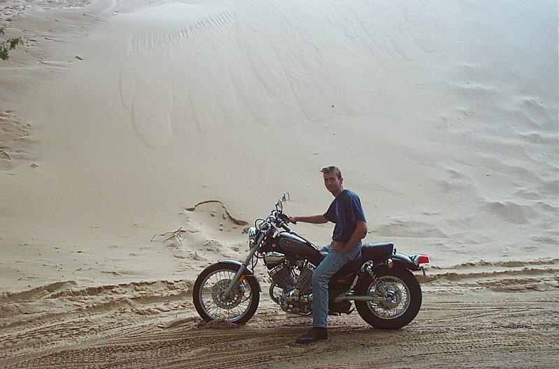 Adam on his bike in front of the dunes