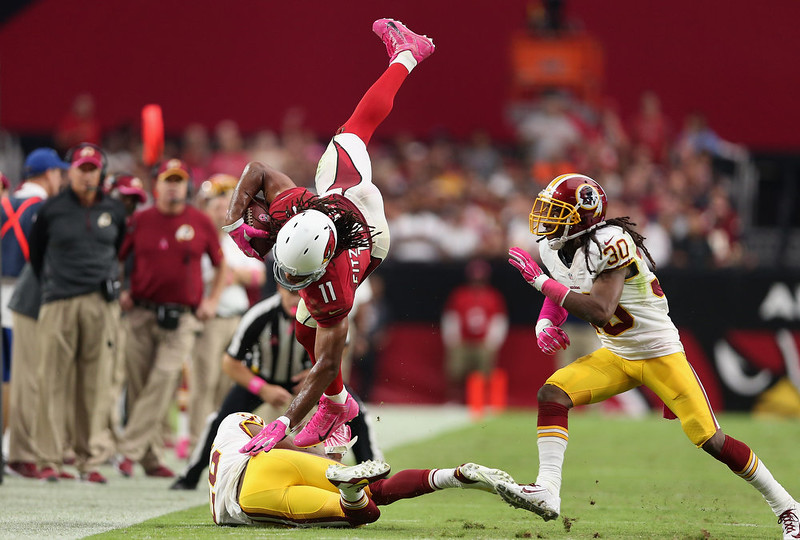 . Wide receiver Larry Fitzgerald #11 of the Arizona Cardinals leaps over strong safety Bashaud Breeland #26 of the Washington Redskins after a reception during the fourth quarter of the NFL game at the University of Phoenix Stadium on October 12, 2014 in Glendale, Arizona. The Cardinals defeated the Redskins 30-20.  (Photo by Christian Petersen/Getty Images)