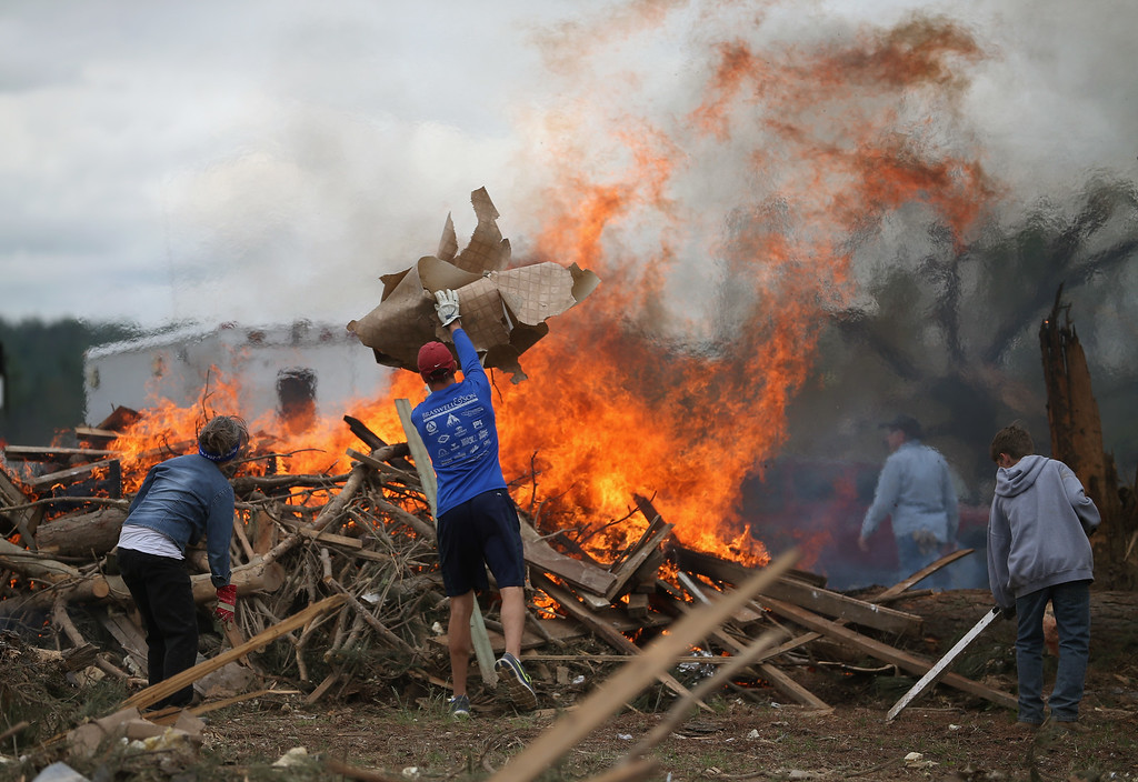 . Volunteers throw tornado debris in a burn pile, April 30, 2014 in Vilonia, Arkansas. Deadly tornadoes ripped through the region starting on April 27 leaving more than two dozen dead. The storm system has also brought severe flooding to Florida\'s Panhandle.  (Photo by Mark Wilson/Getty Images)