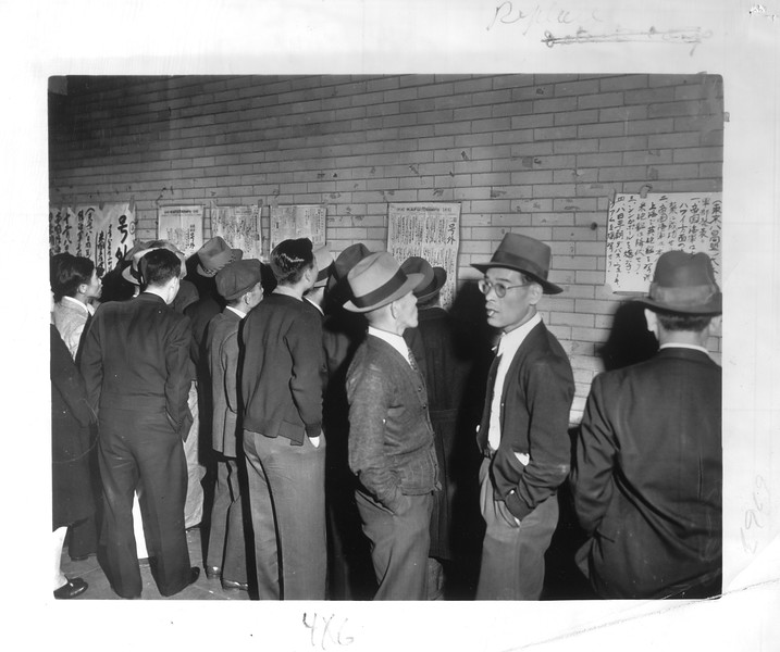 """""""Japanese in Little Tokyo are shown watching bulletins as the war started.  Here is a bulletin posted on a wall of one of the buildings.  Many were shocked, angered by the Japanese government action.""""--caption on photograph"""