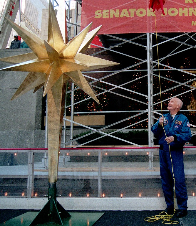 . Senator John Glenn unveils the 12-foot-tall gold star to be placed atop New York\'s Rockefeller Center\'s 75-foot-tall Christmas tree Monday, Nov. 16, 1998. Thirty-six years ago, John Glenn circled the earth three times, and his trip was feted with a ticker tape parade through the Canyon of Heroes, a parade that will occur again later today to honor Glenn for becoming the oldest man ever in space. (AP Photo/Jeff Geissler)
