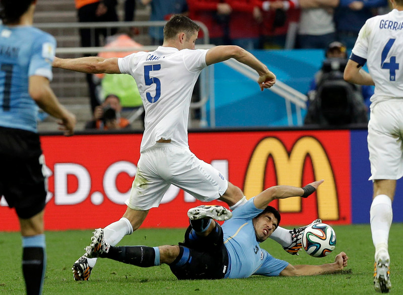 . Uruguay\'s Luis Suarez is challenged by England\'s Gary Cahill during the group D World Cup soccer match between Uruguay and England at the Itaquerao Stadium in Sao Paulo, Brazil, Thursday, June 19, 2014. (AP Photo/Thanassis Stavrakis)