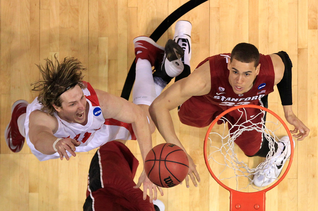 . New Mexico\'s Cameron Bairstow, left, heads to the basket as Stanford\'s Dwight Powell watches during the first half of a second-round game in the NCAA college basketball tournament Friday, March 21, 2014, in St. Louis. (AP Photo/Jeff Roberson)