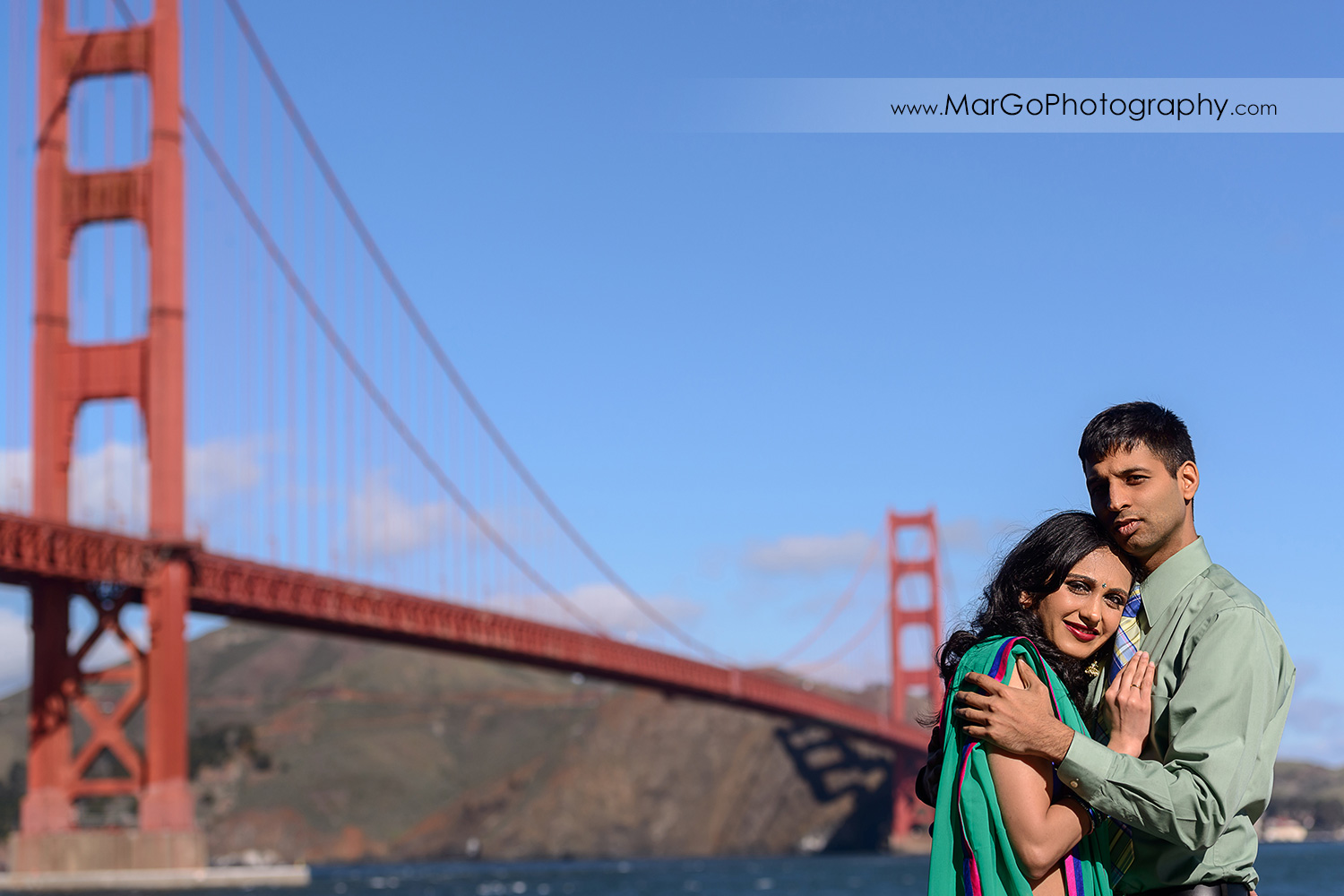 portrait of Indian couple with San Francisco Golden Gate Bridge in background during engagement session