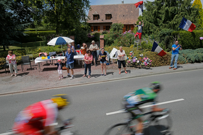 . Spectators wave the French flag as France\'s Thomas Voeckler, right, and Spain\'s Louis Angel Mate Mardones, pass as they ride in the breakaway during the fourth stage of the Tour de France cycling race over 163.5 kilometers (101.6 miles) with start in Le Touquet and finish in Lille, France, Tuesday, July 8, 2014. (AP Photo/Christophe Ena)