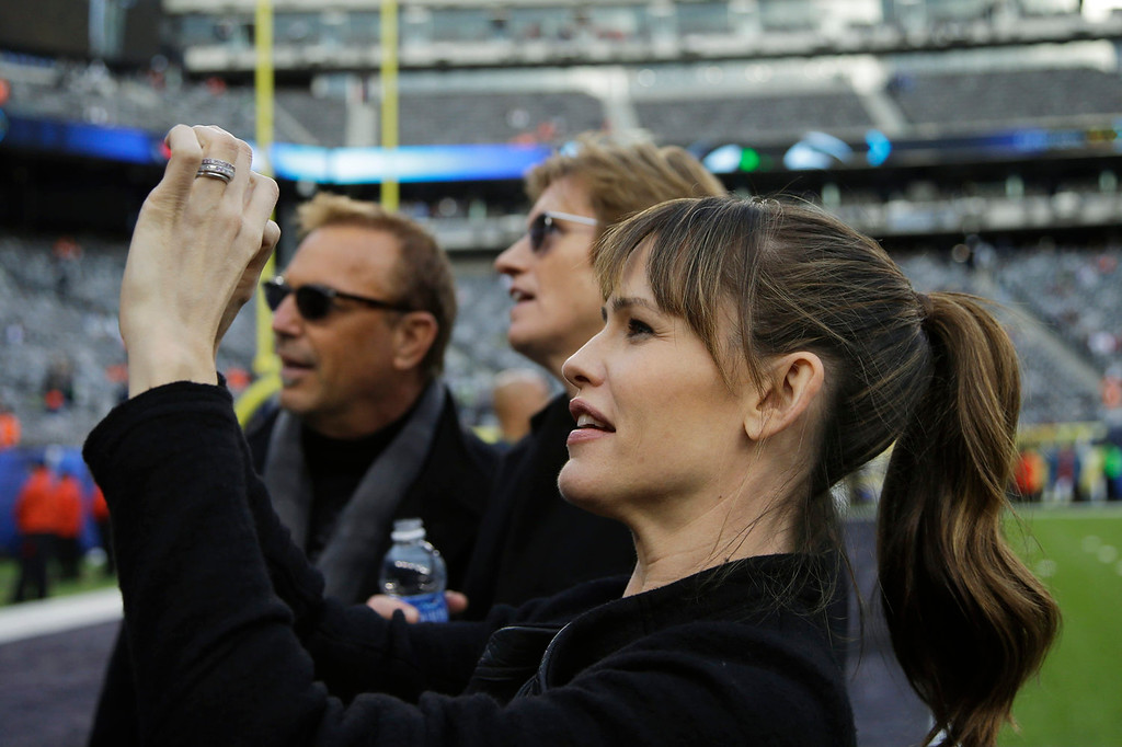 . Actress Jennifer Garner takes a photo as actors Kevin Costner, left, and Denis Leary look on, at MetLife Stadium before the NFL Super Bowl XLVIII football game between the Seattle Seahawks and the Denver Broncos Sunday, Feb. 2, 2014, in East Rutherford, N.J. (AP Photo/Matt Slocum)