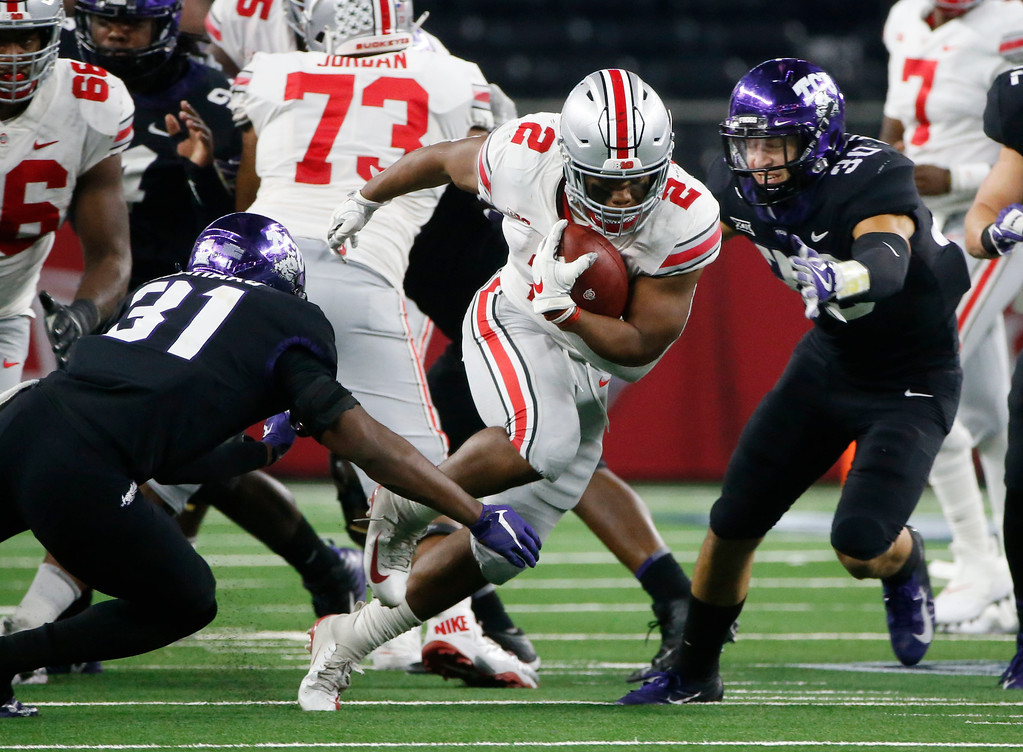 . Ohio State running back J.K. Dobbins (2) tries to avoid a tackle against TCU safety Ridwan Issahaku (31) and TCU linebacker Garret Wallow (30) during the second half of an NCAA college football game in Arlington, Texas, Saturday, Sept. 15, 2018. Ohio State won 40-28. (AP Photo/Michael Ainsworth)