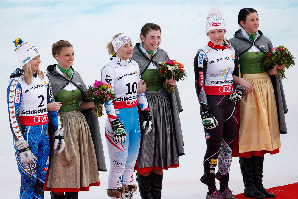 Description of . United States\' gold medal winner Mikaela Shiffrin, Austria\'s silver medal winner Michaela Kirchgasser and Sweden\'s bronze medalist Frida Hansdotter, from right, are lead to the flower ceremony after the women\'s slalom at the Alpine skiing world championships in Schladming, Austria, Saturday, Feb.16, 2013. (AP Photo/Matthias Schrader)
