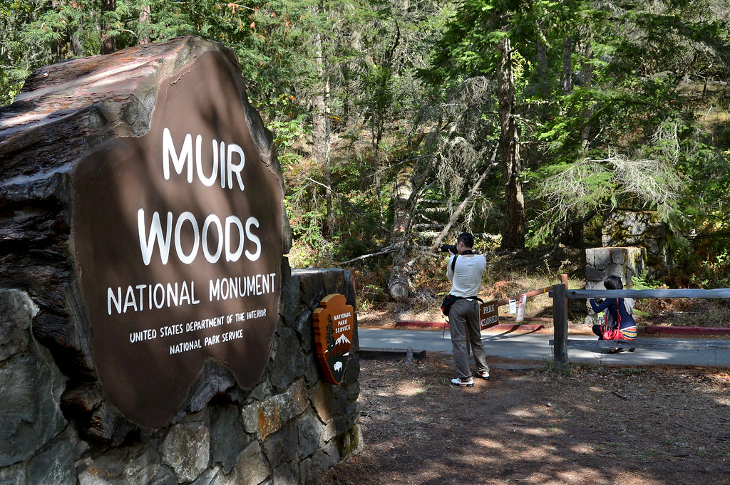 . Liu Ju, left, and Ning Quong of Guangzhou, China, take photos from the entrance to Muir Woods National Monument in Mill Valley, Calif. on Tuesday, Oct. 1,  2013. The park was closed due to the partial federal government shutdown. (Alan Dep/Marin Independent Journal)