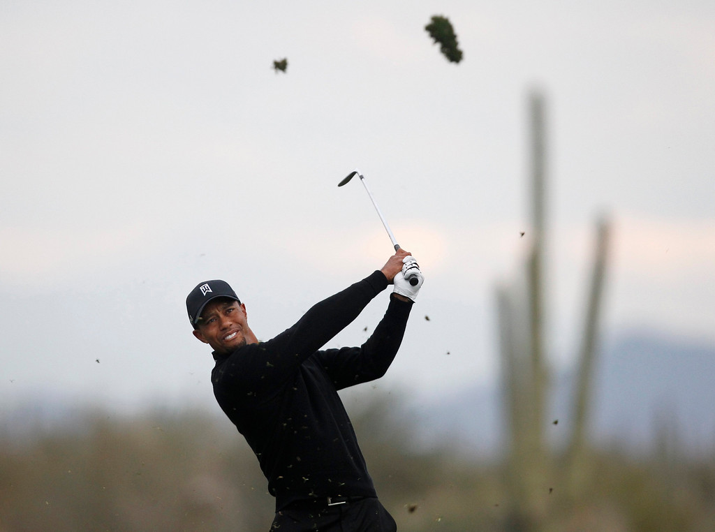 . Tiger Woods of the U.S. hits a fairway shot on the 14th hole against Charlies Howell III of the U.S. during the weather-delayed first round of the WGC-Accenture Match Play Championship golf tournament in Marana, Arizona February 21, 2013. REUTERS/Matt Sullivan