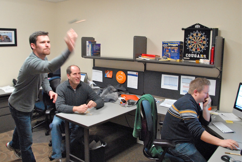2011/2/1 – A few days ago (1-24) I shot my guys throwing darts using a camera that shot 10 frames a second. The quality wasn't what I wanted so I tried it again with one of my expensive cameras. This is shot with the natural light in the office at a slow shutter speed (1/50th of a second). That gives the nice blur as the dart leaves Ryan's hand. This is 3 of the five guys in my marketing group.