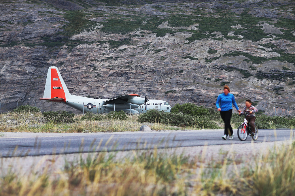 . People walk past as pilot from the New York Air National guard prepares to take off in the ski-equipped National Science Foundation C-130 on July 11, 2013 in Kangerlussuaq, Greenland.   (Photo by Joe Raedle/Getty Images)