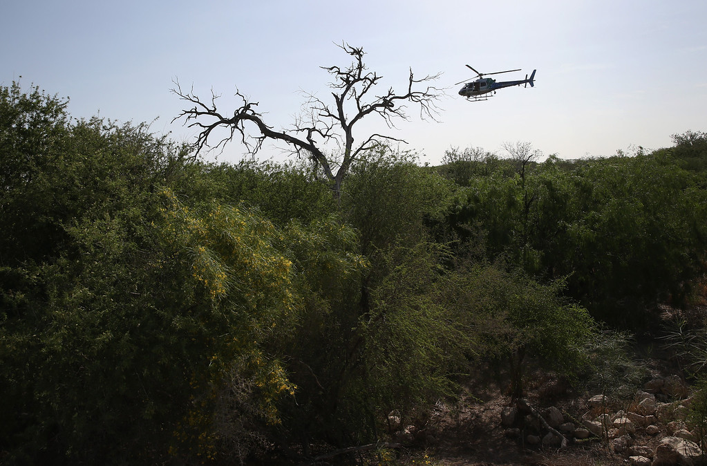 . MISSION, TX - APRIL 11:  A U.S. Air and Marine helicopter searches for undocumented immigrants in thick brush near the U.S.-Mexico border on April 11, 2013 in Mission, Texas. Air and Marine agents helped U.S. Border Patrol Agents detain a group of 16 immigrants from Mexico and El Salvador said they crossed the Rio Grande River from Mexico into Texas during the morning hours before they were caught. The Rio Grande Valley sector of has seen more than a 50 percent increase in illegal immigrant crossings from last year, according to the Border Patrol. Agents say they have also seen an additional surge in immigrant traffic since immigration reform negotiations began this year in Washington D.C. Proposed refoms could provide a path to citizenship for many of the estimated 11 million undocumented workers living in the United States. Photo by John Moore/Getty Images)  (Photo by John Moore/Getty Images)