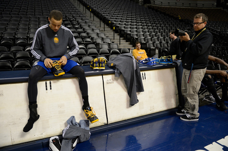 . NBA Photographer Garrett Ellwood looks on as Stephen Curry (30) of the Golden State Warriors ties his shoes before practice April 22, 2013 at Pepsi Center. The Golden State Warriors prepare for game two of the first round of the NBA playoffs against the Denver Nuggets. (Photo By John Leyba/The Denver Post)