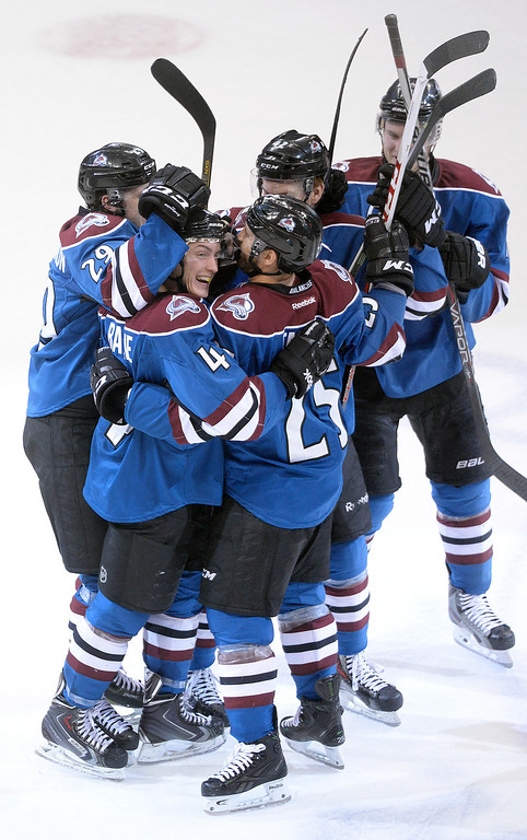 . DENVER, CO - MARCH 27: Tyson Barrie (4) was mobbed by teammates after his game winning goal in overtime Thursday night.  The Colorado Avalanche defeated the Vancouver Canucks 3-2 in overtime Thursday night, March 27, 2014 at the Pepsi Center in Denver, Colorado. (Photo by Karl Gehring/The Denver Post)