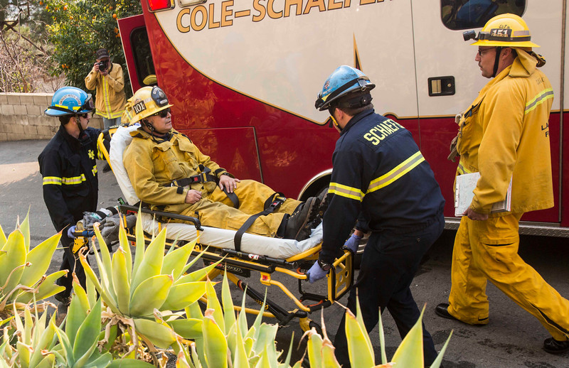 . A injured firefighter is transported to an ambulance as a wildfire burns just north of the San Gabriel Valley community of Glendora, Calif., on Thursday, Jan 16, 2014. Southern California authorities have ordered the evacuation of homes at the edge of a fast-moving wildfire burning in the dangerously dry foothills of the San Gabriel Mountains. (AP Photo/Ringo H.W. Chiu)