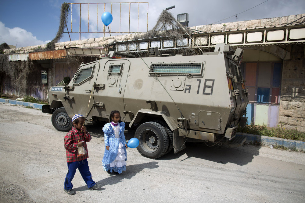 . Children of Israeli settlers wearing costumes walk past an army vehicle as they celebrate the annual Purim parade on February 24, 2013 in the occupied West Bank city of Hebron. Purim commemorates the salvation of the Jews from the ancient Persians as described in the biblical book of Esther. MENAHEM KAHANA/AFP/Getty Images