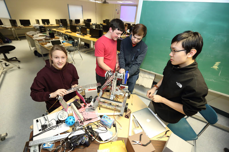 Some of the robotics club members, from left: Kiara Munz, Isaac Noble, Sean McNamara, and Jeffrey Young discuss where to place the motors for a four-wheel drive robot.