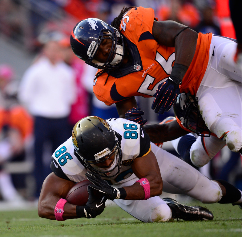 . Denver Broncos outside linebacker Nate Irving (56) tackles Jacksonville Jaguars tight end Clay Harbor (86) in the third quarter.  (Photo by AAron Ontiveroz/The Denver Post)