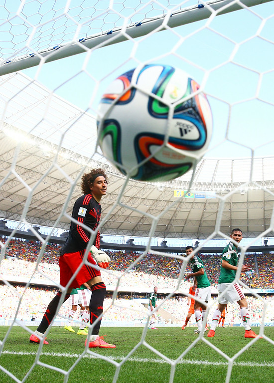 . Wesley Sneijder of the Netherlands scores his team\'s first goal past Guillermo Ochoa of Mexico during the 2014 FIFA World Cup Brazil Round of 16 match between Netherlands and Mexico at Castelao on June 29, 2014 in Fortaleza, Brazil.  (Photo by Dean Mouhtaropoulos/Getty Images)