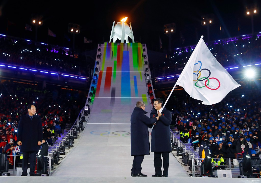 . International Olympic Committee President Thomas Bach, center, hands the Olympic flag to the mayor of Beijing, China, Chen Jining, during the closing ceremony of the 2018 Winter Olympics in Pyeongchang, South Korea, Sunday, Feb. 25, 2018. Sim Jae-guk, the mayor of Pyeongchang, South Korea, is at left. (Kai Pfaffenbach/Pool Photo via AP)