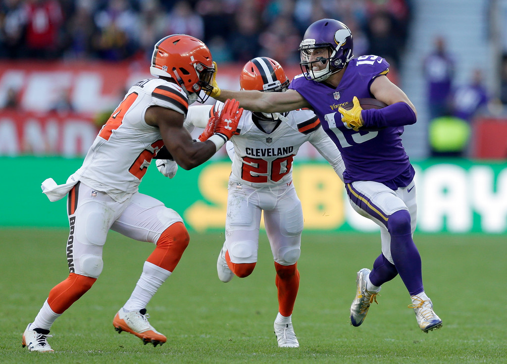 . Minnesota Vikings wide receiver Adam Thielen, right, holds off Cleveland Browns\' Ibraheim Campbell, left, and Briean Boddy-Calhoun (20) during the first half of an NFL football game at Twickenham Stadium in London, Sunday Oct. 29, 2017. (AP Photo/Tim Ireland)