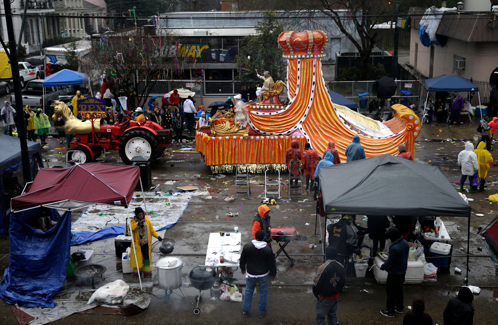 Description of . King of the Krewe of Rex, Jack Laborde, rides on his float down a largely empty St. Charles Ave., during Mardi Gras day in New Orleans, Tuesday, March 4, 2014. Rain and unusually cold temperatures kept the normally massive and festive crowds away. (AP Photo/Gerald Herbert)