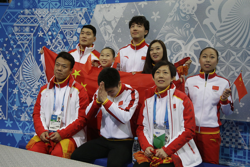 ". China\'s Yan Han (C) stands with his team in the ""kiss and cry\"" zone after performing in the Men\'s Figure Skating Team Short Program at the Iceberg Skating Palace during the Sochi Winter Olympics on February 6, 2014. (DARRON CUMMINGS/AFP/Getty Images)"