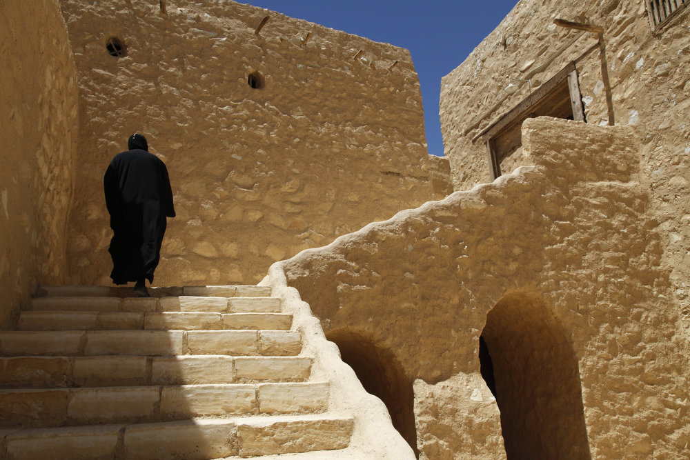 . A monk walks on the grounds of the ancient monastery of St. Anthony, southeast of Cairo, Egypt on Tuesday, April 16, 2013. Tucked away in the vast and barren eastern Egyptian desert, the gentle manners and soft voices of the monks are a perfect fit for the peace and tranquility of St. Anthony, nestling at the foot of an imposing rock mountain deep in the desert. A spring had until several years ago been the sole source of water for the monks, their date palms and olive trees.  (AP Photo/Manoocher Deghati)