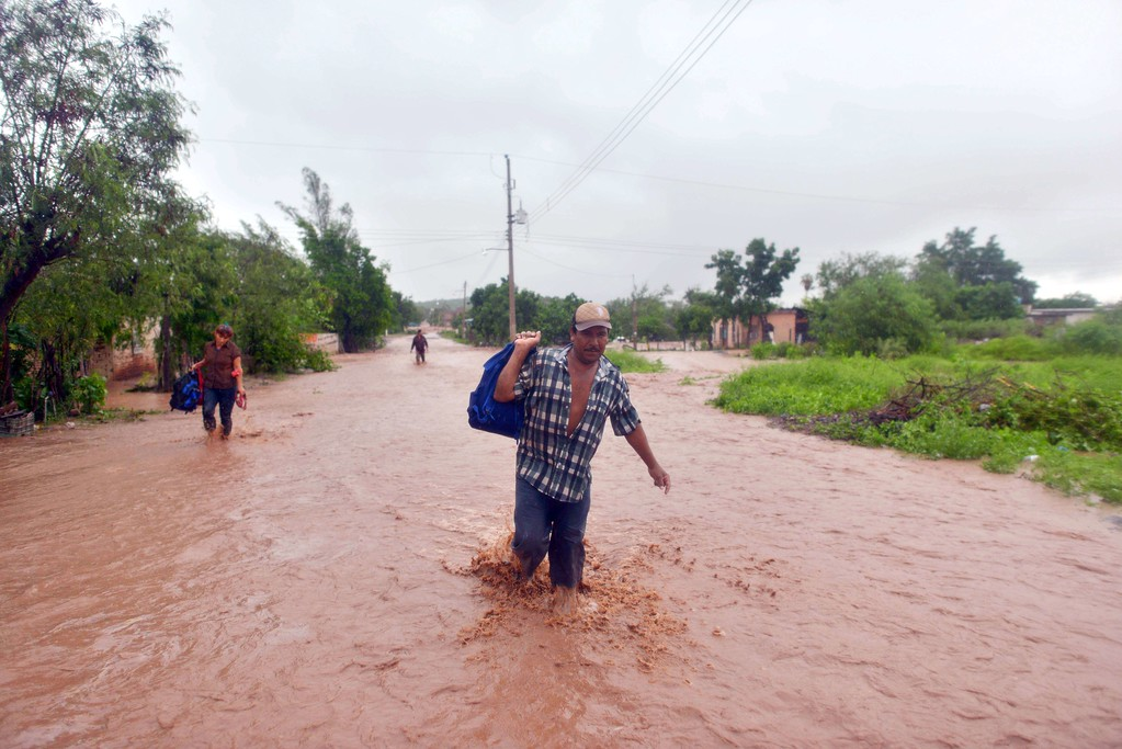 . Residents of El Zapotillo evacuate their homes because of the overflooding of the neighboring river, in the state of Sinaloa, Mexico, on September 19, 2013. Deaths from floods and landslides battering Mexico neared 100 on Thursday as a fresh hurricane hit the northwest and rescuers faced a risky mission in a village buried in mud.  Fernando Brito/AFP/Getty Images