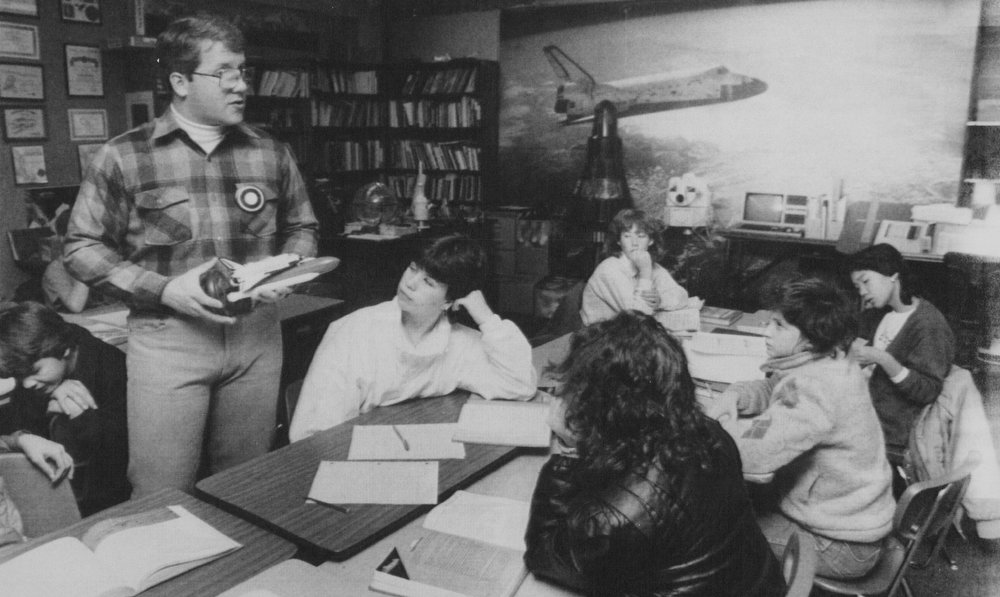 Description of . Laurin Intermediates School seventh grade teacher Mike Murray of Battle Ground, Wash., who was a finalist in the contest to choose a teacher for the Challenger space shuttle flight, holds a model of the shuttle as he tries to explain to his class Tuesday why the shuttle exploded killing seven crew members, including the first teacher in space. 1986  Credit: AP Laserphoto