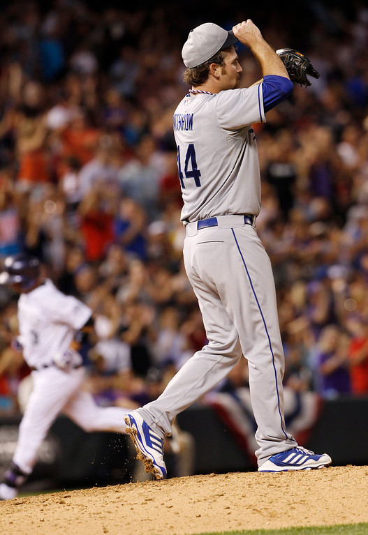 . Los Angeles Dodgers relief pitcher Chris Withrow, front, reacts after giving up a solo home run to Colorado Rockies\' Michael Cuddyer, back, in the seventh inning of the Rockies\' 9-5 victory in a baseball game in Denver, Thursday, July 4, 2013. (AP Photo/David Zalubowski)