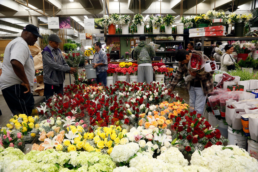 . Buyers at the Flower Market look over Valentine\'s Day flowers for purchase, Friday Feb. 14, 2014 in Los Angeles. (AP Photo/Nick Ut)
