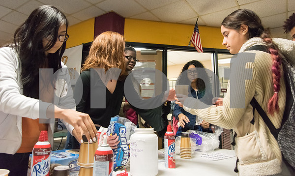 12/06/17 Wesley Bunnell   Staff Claire Palin hands a cup of hot chocolate to fellow student Kiaraliz Colon, R, as part of the New Britain High School Interact Club's fundraising efforts to benefit Warm the Children on Wednesday October 29th. Fellow club members Joann Khambaylarsirkul, L, Savannah Newton and Abigail Rivera are shown.