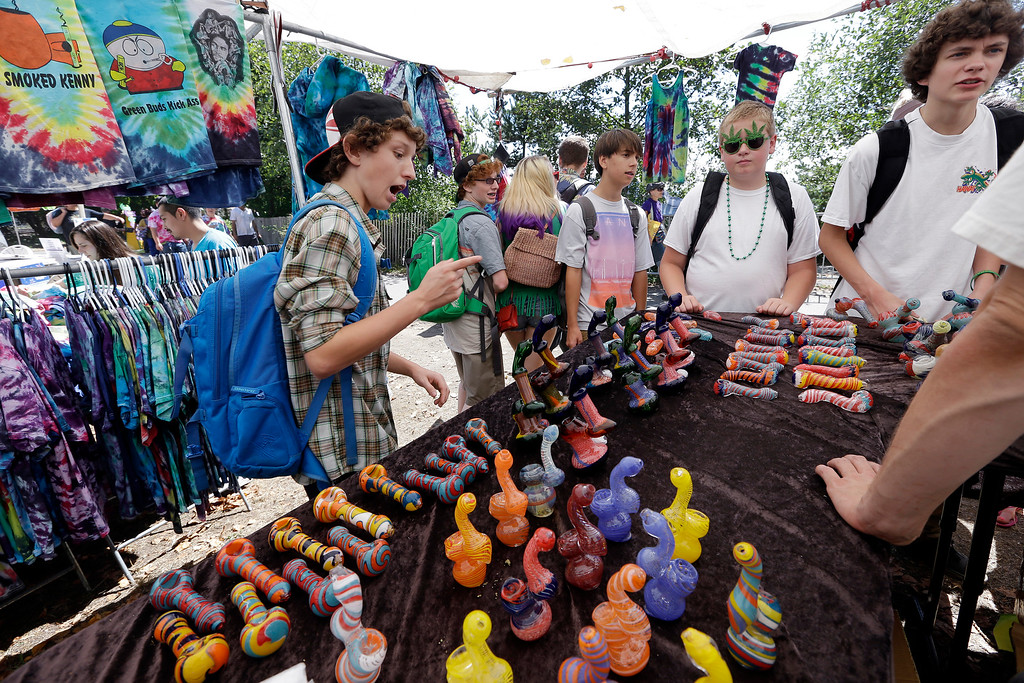 . A group of teenaged boys look over a display of glass pipes at the first day of Hempfest, Friday, Aug. 16, 2013, in Seattle. Thousands packed the Seattle waterfront park for the opening of a three-day marijuana festival ó an event that is part party, part protest and part victory celebration after the legalization of pot in Washington and Colorado last fall. Hempfest was expected to draw as many as 85,000 people per day. (AP Photo/Elaine Thompson)