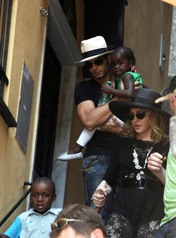 """. Photo taken Monday Aug. 17, 2009 made available Tuesday Aug. 18, 2009 of U.S. singer Madonna, at right, holding hands with her adopted child from Malawi David Banda, bottom left, followed by Brazilian model Jesus Luz, top  left, holding her other adopted child Chifundo \""""Mercy\"""" James, in Italy\'s northwestern riviera town of Portofino. Reports said Tuesday Madonna is in the seaside resort town to spend some time with Italian designers Dolce and Gabbana and other friends. After adopting David Banda in 2008, Malawi\'s highest court had granted the adoption of Chifundo \""""Mercy\"""" James June 12, 2009 overturning an April lower court ruling that Madonna had not spent enough time in Malawi to be given a child. Madonna\'s Raising Malawi, a charity founded in 2006, helps feed, educate and provide medical care for some of Malawi\'s orphans.  (AP Photo)"""