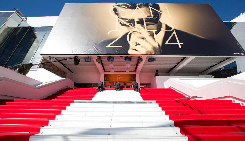 . Workers prepare the red carpet on the stairs of the Palais des Festivals prior to the start of the 67th international film festival, Cannes, southern France on Wednesday, May 14, 2014. The festival runs from May 14th to May 25th. (AP Photo/Virginia Mayo)