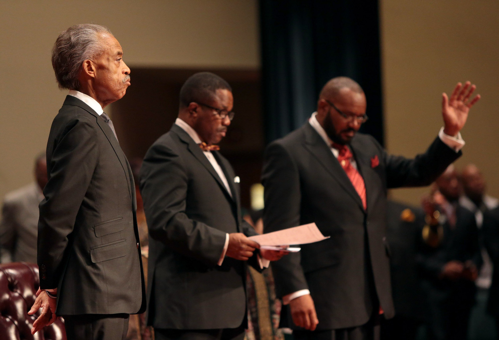 Description of . The Rev. Al Sharpton, left, attends the funeral services for 18-year-old Michael Brown on Monday, Aug. 25, 2014, at Friendly Temple Missionary Baptist Church in St. Louis. Hundreds of people gathered to say goodbye to Brown, who was shot and killed by a Ferguson, Mo., police officer on Aug. 9. At center is church Pastor Michael Jones and at right is Pastor Charles Ewing, an uncle of Michael Brown. (AP Photo/St. Louis Post Dispatch, Robert Cohen, Pool)