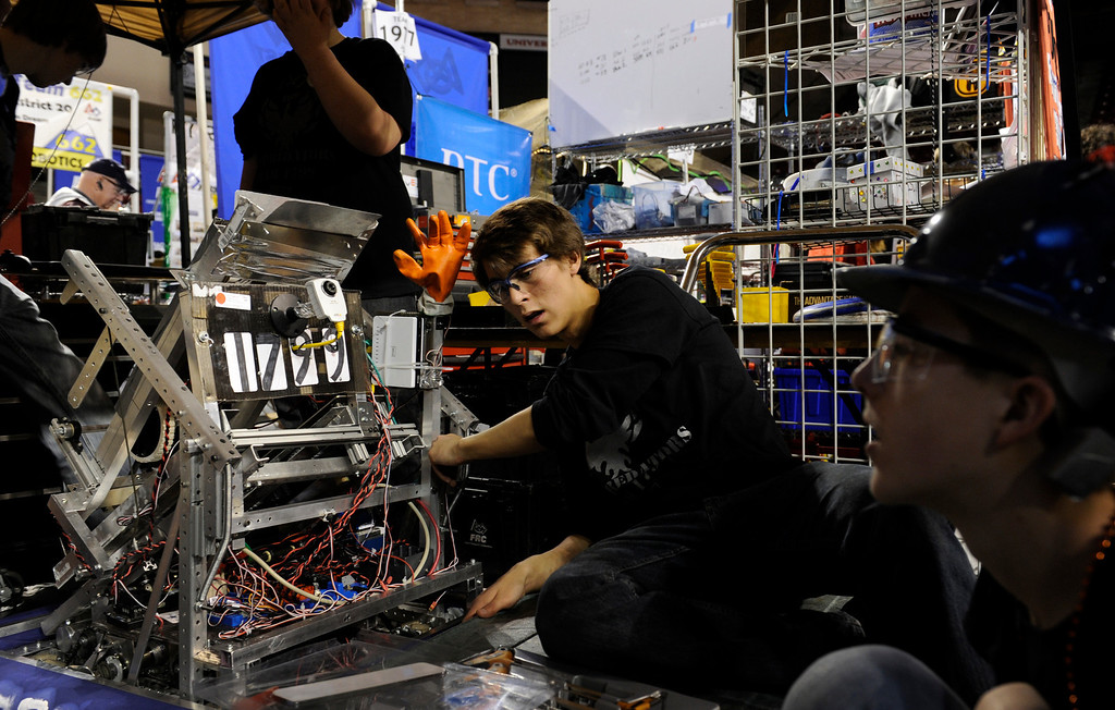 . DENVER, CO.- APRIL 6: A collaborative team from some Littleton schools perform maintenance work on their robot including Kendrick Hougen, 17, center from Chatfield High School, and Tyler Ennis, 17, right, from Dakota Ridge High School. The Colorado Regional FIRST Robotics Competition takes place in Magness Arena inside the Ritchie Center on the University of Denver campus. High School students from all over the state, region, and even a team from Mexico, participate in a high-tech spectator sporting event (this year the teams used frisbees) using specially engineered robots that are maneuvered by human drivers using computers and joy sticks.(Photo By Kathryn Scott Osler/The Denver Post)