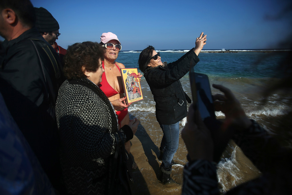 . A woman takes photographs of herself with a swimmer holding an icon after catching the cross into the water during an epiphany ceremony to bless the sea waters at Famagousta or Varosia beach in the Turkish Cypriots breakaway north part of the eastern Mediterranean divided island of Cyprus, Friday, Jan 6, 2017. Many Orthodox Christian faithful attended the Epiphany Day blessing of the waters in Famagusta in Cyprus\', the second time the ceremony has taken place since 1974 when the small island nation was cleaved along ethnic lines. (AP Photo/Petros Karadjias)