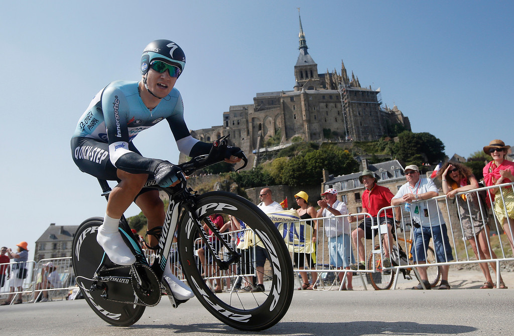 . Michal Kwiatkowski of Poland passes world heritage site Mont-Saint-Michel, rear, a rocky tidal island which holds a monastery, during the eleventh stage of the Tour de France cycling race, an individual time trial over 33 kilometers (20.6 miles) with start in in Avranches and finish in Mont-Saint-Michel, western France, Wednesday July 10 2013. (AP Photo/Laurent Cipriani)