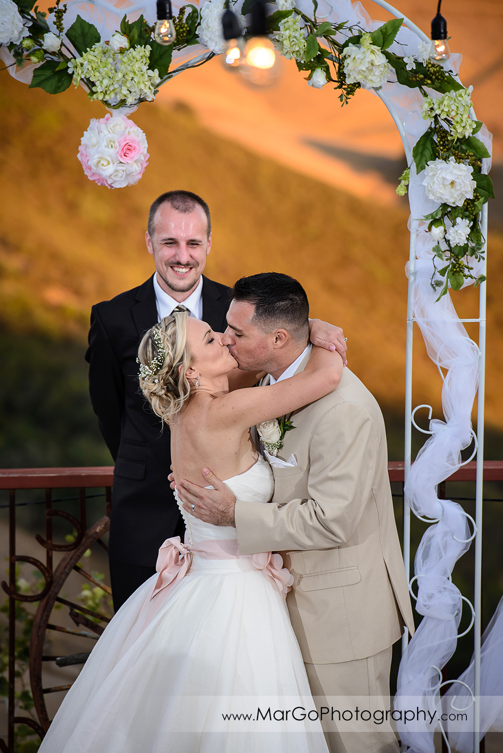 bride and groom kissing after backyard wedding ceremony
