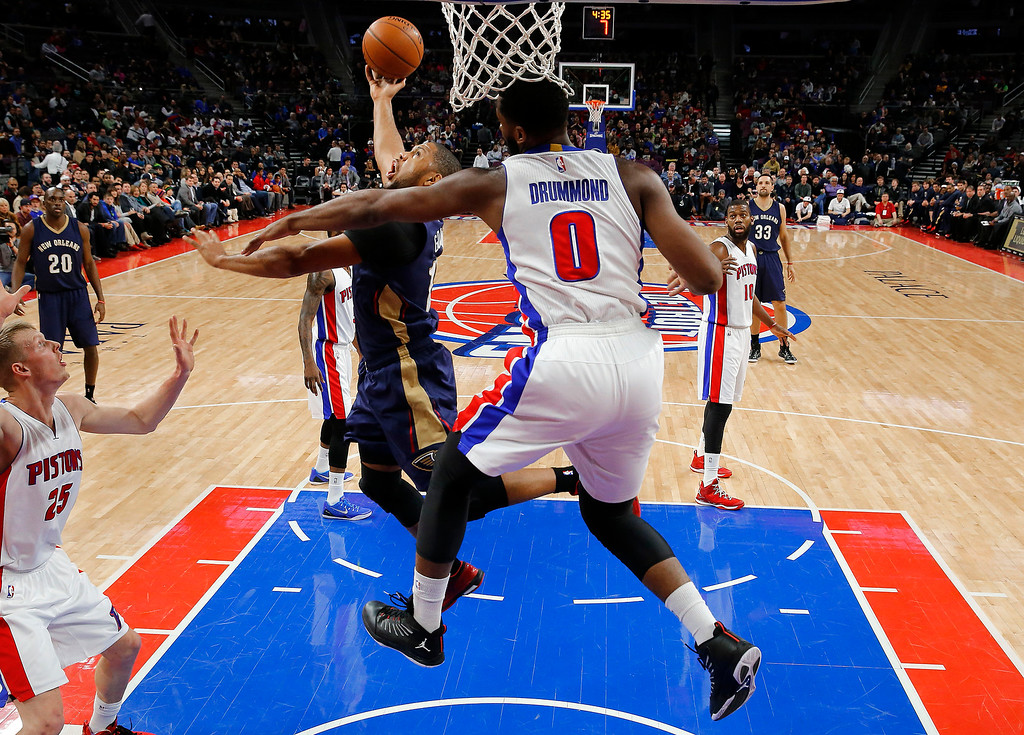 . Detroit Pistons center Andre Drummond (0) defends New Orleans Pelicans guard Eric Gordon during the first half of an NBA basketball game in Auburn Hills, Mich., Wednesday, Jan. 14, 2015. (AP Photo/Paul Sancya)