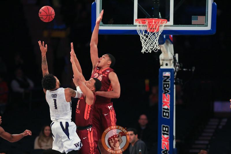 Washington's guard David Crisp (1) lofts a shot over Virginia Tech's guard Justin Robinson (5) and forward Kerry Blackshear Jr. (24) in Madison Square Garden, Nov. 17, 2017. Virginia Tech won the game 103-79.